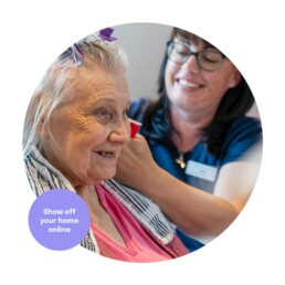 Care Home Resident having her hair done with a carer. Photography for care homes.